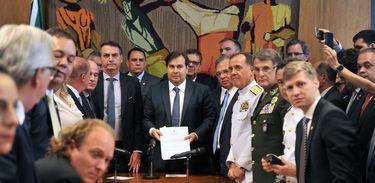 ボウソナロ大統領(中央左)と、受け取ったばかりの軍関係者年金改革法案を見せるロドリゴ・マイア議長(J.Batista / Camara dos Deptados)