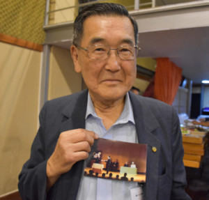式典の写真を持つ桜井仁さん