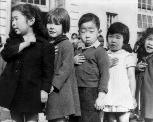 強制収容所内で、合衆国旗への「忠誠の誓い」をする子供たち(1942年4月、Photo attributed to Dorothea Lange(w). [Public domain])