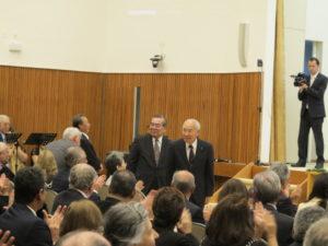教団功労者として会場から拍手をされる斎藤武雄元責任役員(左端)、後ろを向く大野正人元総務部長と林秀有(ひでなり)元本部長