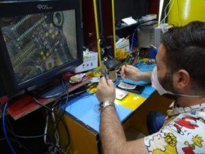 シリア人の友人の店で携帯電話を修理するアブドゥルバセットさん