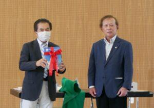 園田副会長から与儀会長へ完成したばかりの60年史プレゼント