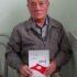海外の移民に関する著書『歳月』を手にする鄭夏源さん