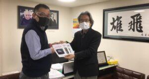 学校法人力行会の田中総務部長から3冊を受け取る加藤代表