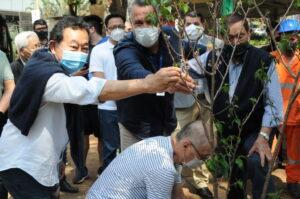 桜を植樹する野村市議(左)とサレス地区長(中央)、右が池崎会長